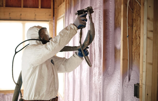 Contractor installing closed cell spray foam in a wall